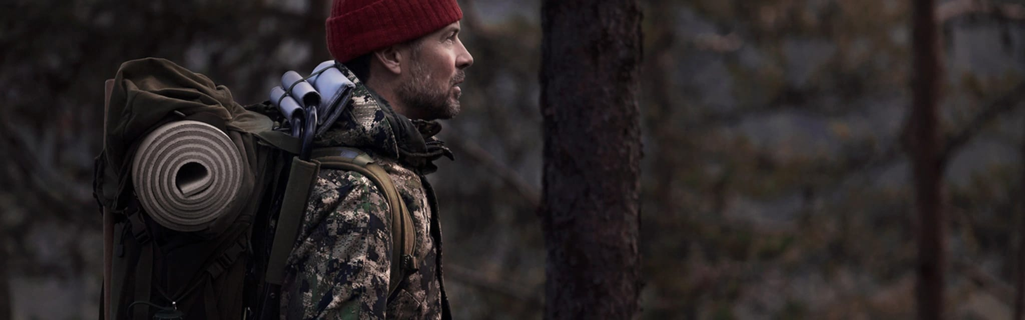 Prepper lifestyle - man with camping backpack in woods