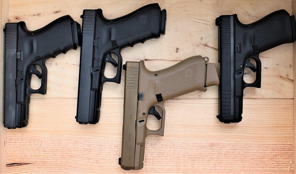 compact glock pistols on table