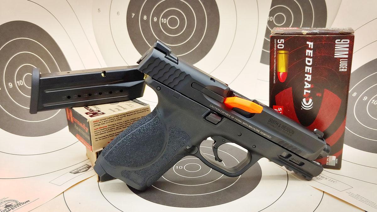handgun with magazine next to paper target