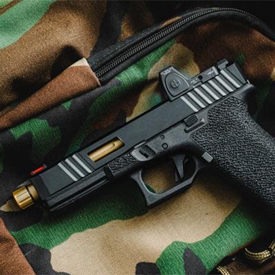 handgun on top of camoflauge bag