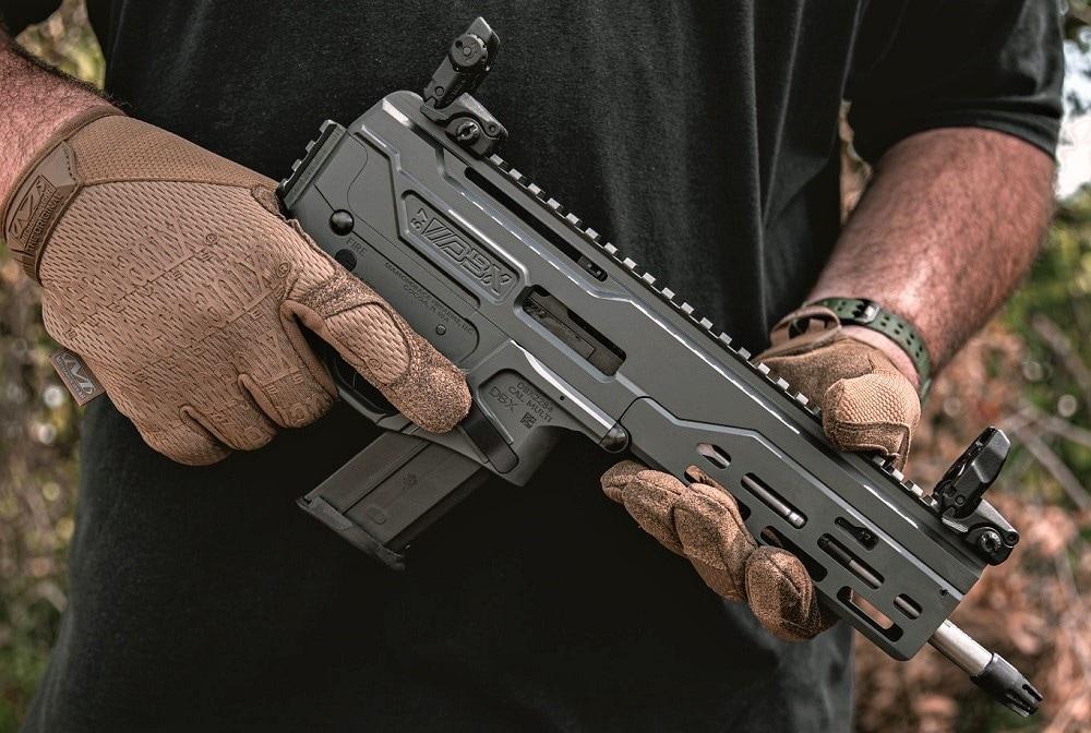 Diamondback DBX 5.7 pistol in dark grey being held by a sweaty man wearing gloves in a jungle setting, possibly Florida