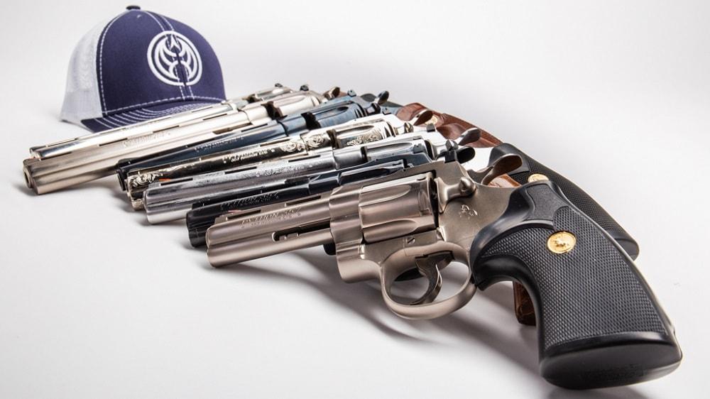 colt pythons next to a guns dot com hat