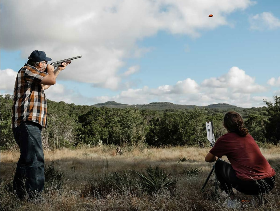 woman and man shooting clay targets outdoors