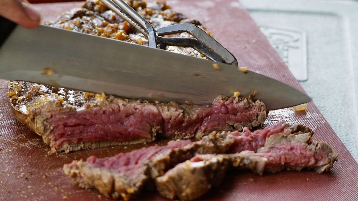 Knife slicing meat on cutting board