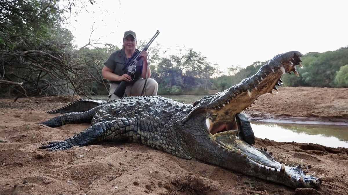 Hunter with henry all-weather lever action by large crocodile