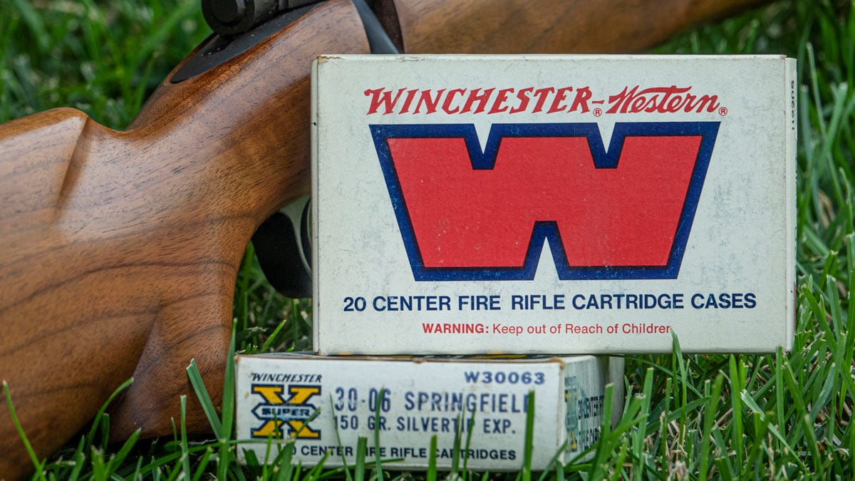 Winchester ammo next to rifle on grass