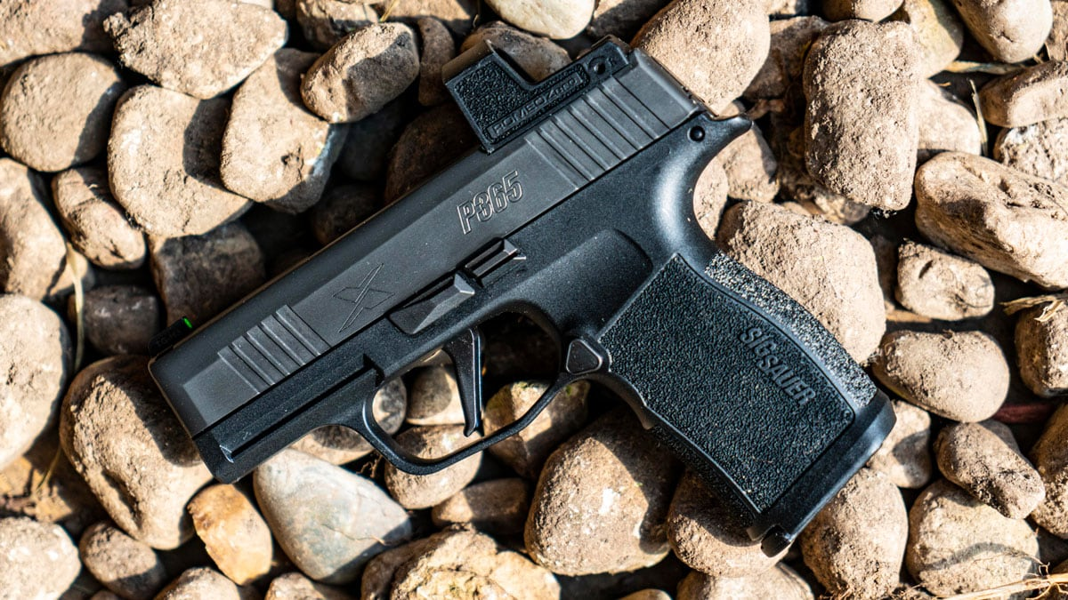 Sig Sauer P365 XL pistol with red dot on rocks