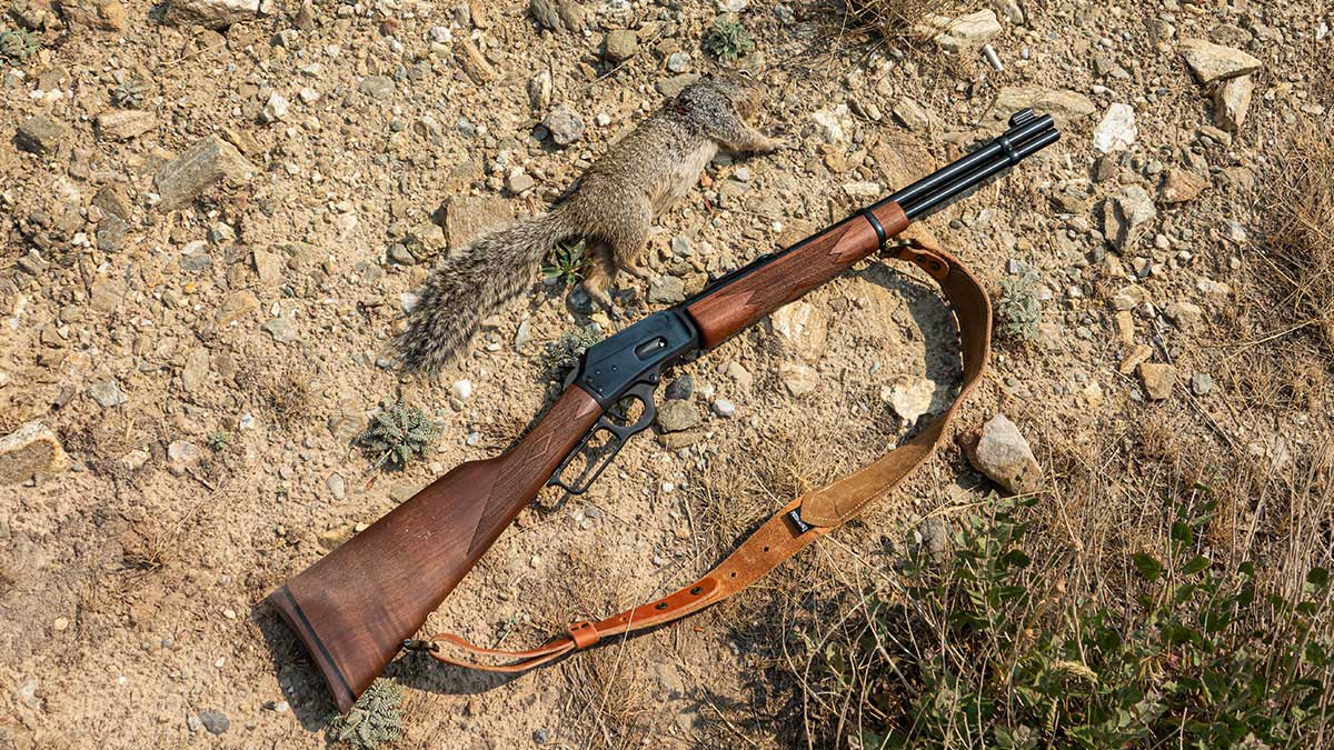 Marlin 1894 laying in the dirt next to a recently shot squirrel