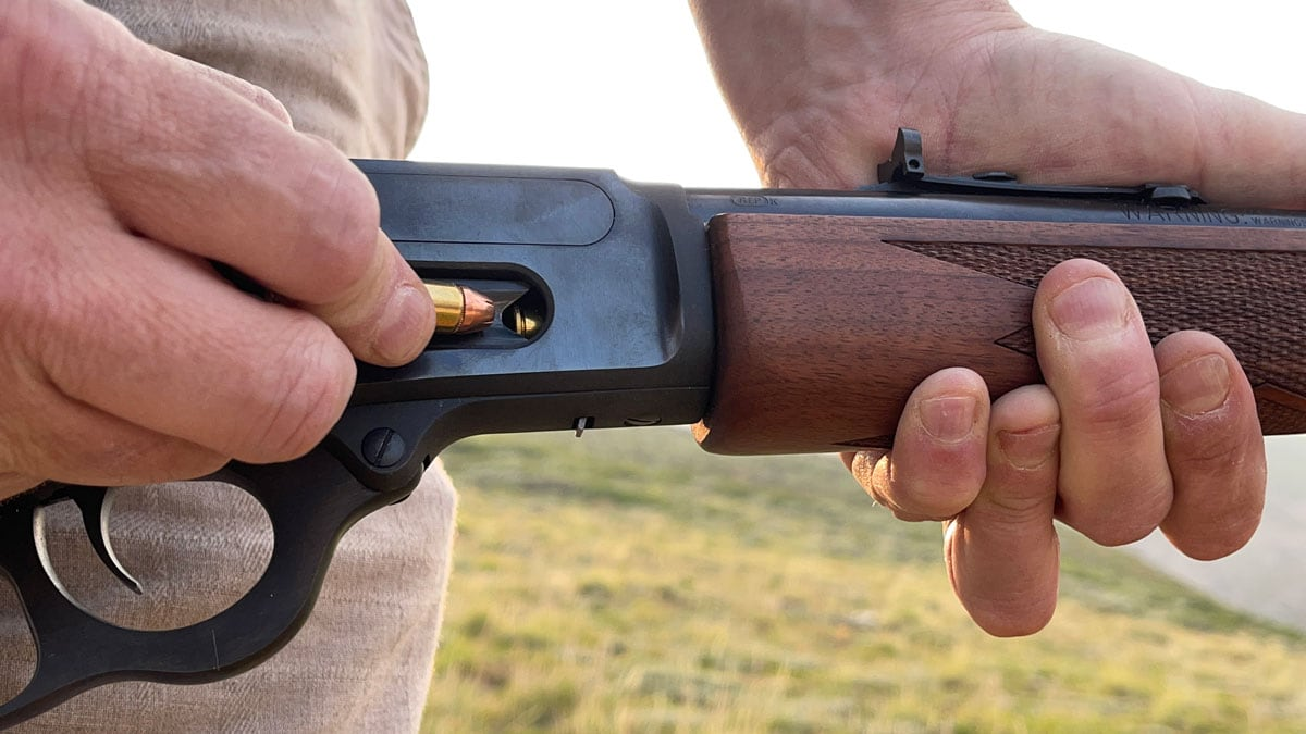 A man reloads his Marin 1894 lever-action rifle