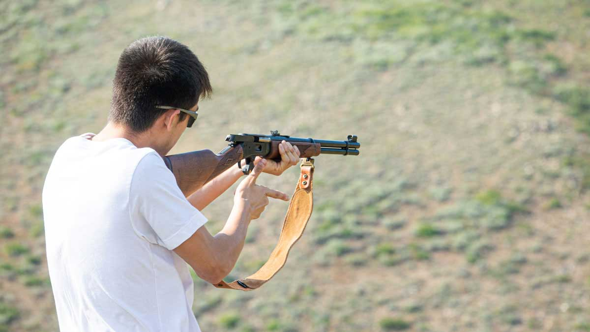 A man shoots the Marlin 1894 lever-action rifle at the range