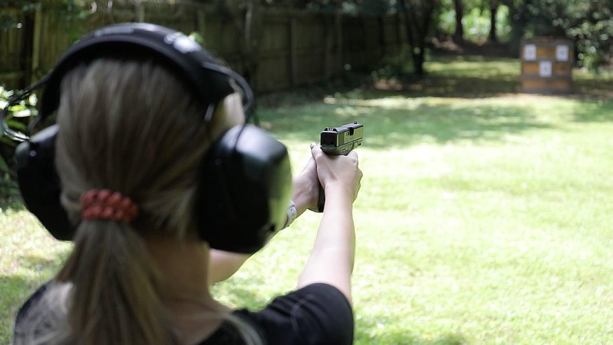 A woman shoots her Glock 19 pistol on the range