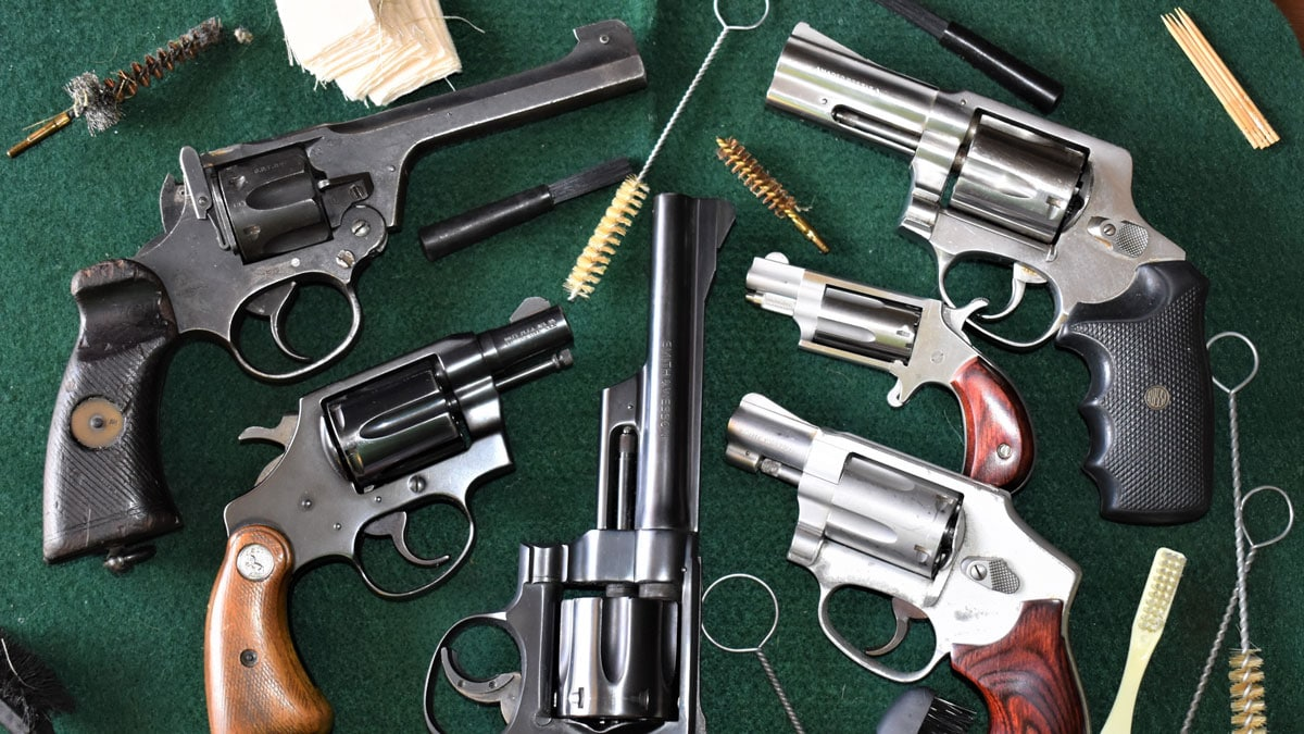 Revolvers sit on a cleaning table with cleaning gear
