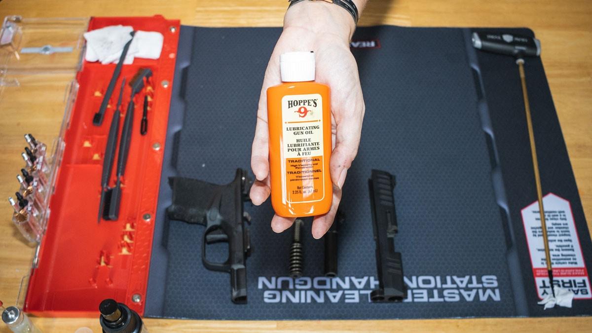 A woman holds a bottle of Hoppe's gun oil