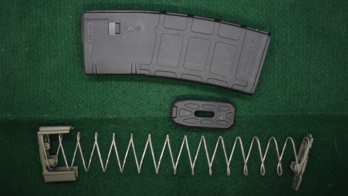A disassembled AR-15 magazine sits on a cleaning table