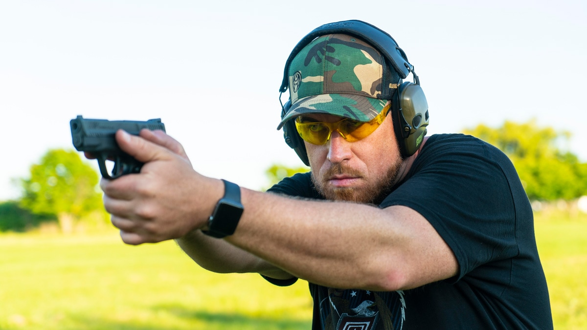 A shooter wears the Guns.com Camo Hat at the range