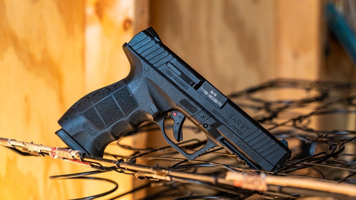 SAR 9 pistol rests on metal rack