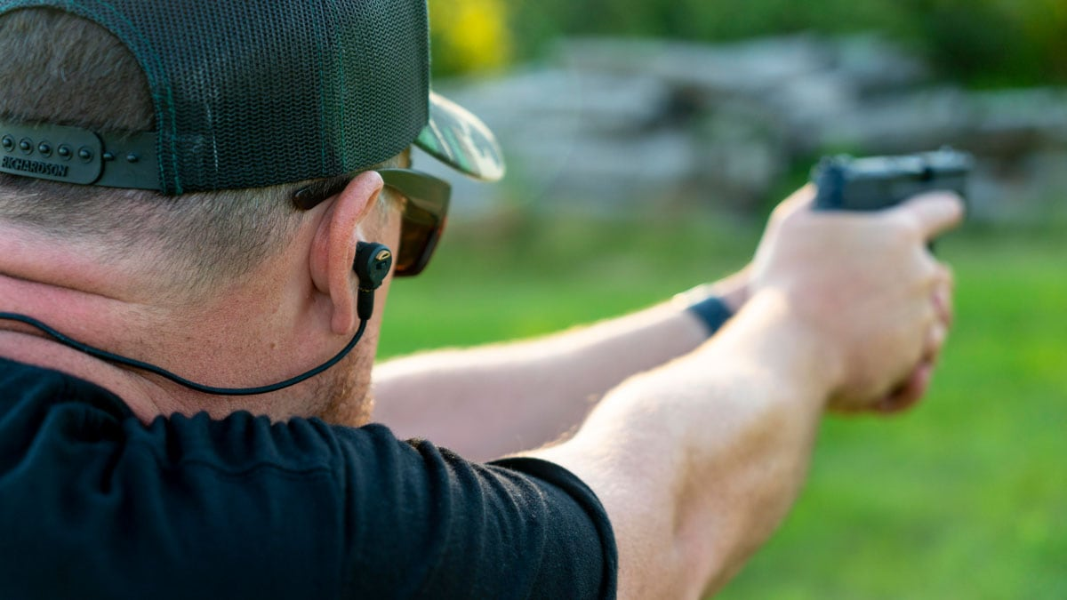 A shooter with hearing protection prepares to fire his pistol
