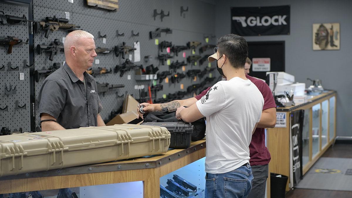 Customers stand at the counter at a gun shop
