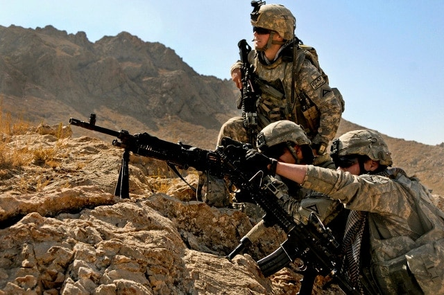 soldiers shooting colt rifle in rocky terrain