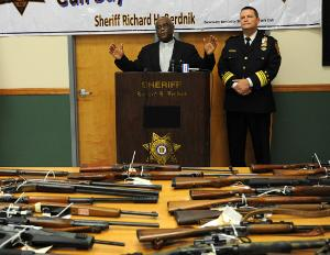 Passaic County officials standing behind a table full of guns