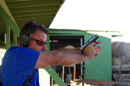 male shooting handgun outside at range
