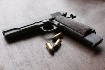 handgun with ammo on table