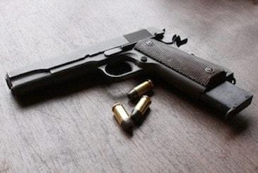 stock photo of handgun on table with ammo