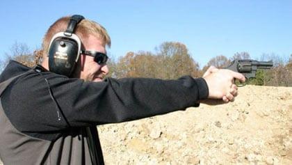man shooting handgun outdoors at sandy range