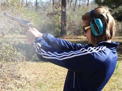 female shooting long barrel revolver outdoors
