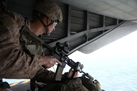 A Marine looks out over the water in the back of a plane with an M4 with a Leupold HAMR scope in his shoulder.