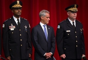 Chicago Mayor Rahm Emanuel standing between two Chicago officers