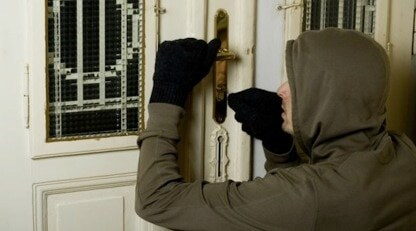 robber picking lock on house