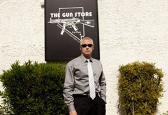 man standing outside gun store