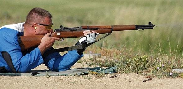 A man firing a rifle