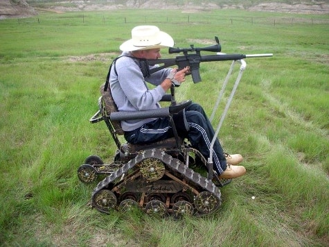 A shooter firing an AR rifle from his Action Trackchair