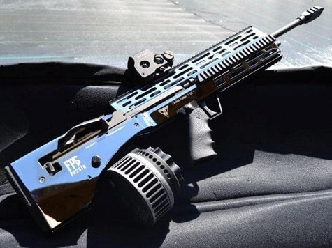 Rifle equipped with Juggernaut stock, drum magazine and holographic sight