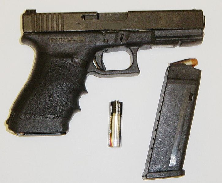 glock 21 with magazine out next to aa battery