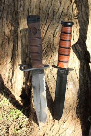 2 ka bar knives sitting next to tree