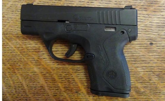 the beretta nano handgun sitting on a table indoors