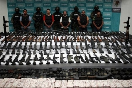 guns seized in mexico laid out on tables