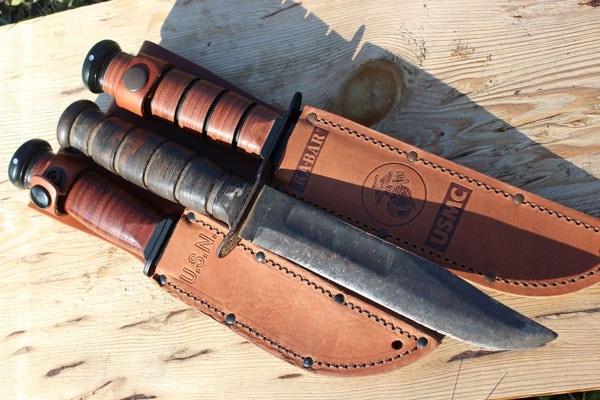 three ka bar knives in leather sleeves