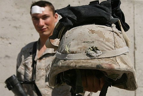 A soldier holding up an ACH helmet that has deflected a bullet