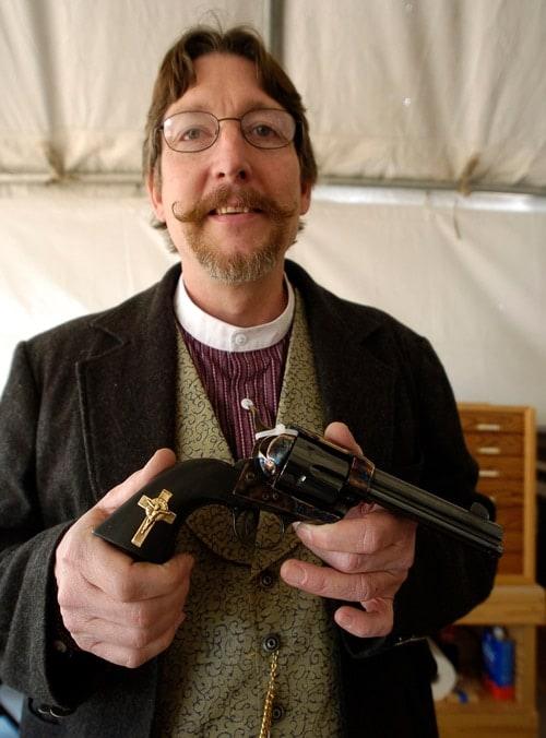 man holding handgun with cross on it