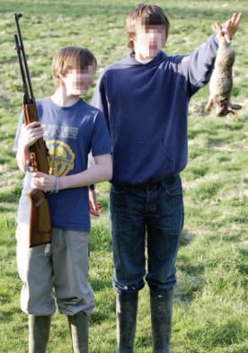 Two boys with blurry faces displaying a dead rabbit. Photo credit: Animal Aid.