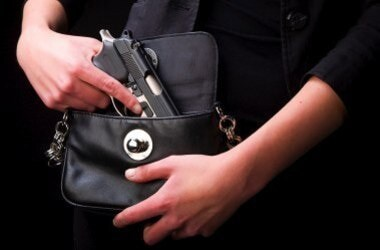 stock photo of handgun being concealed in purse bag