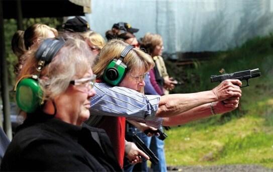 women shooting handguns at outdoor firing range