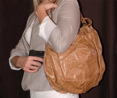 woman pulling handgun out of purse