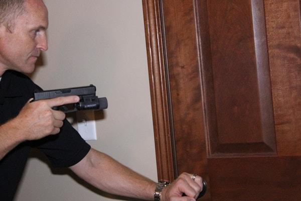 Gaining entry through door with guns.
