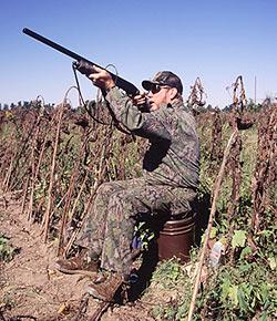 man in camo outdoors firing rifle in sky