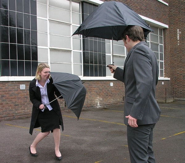 man and a woman posing with umbrellas